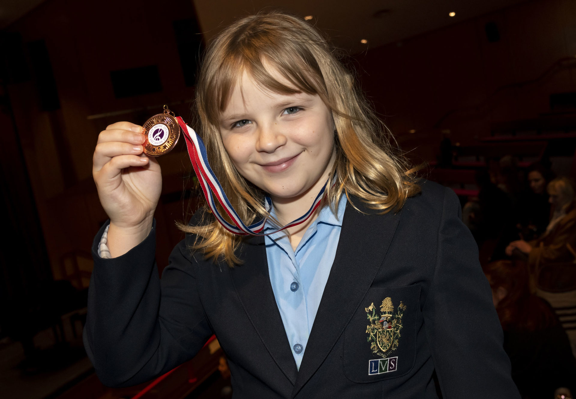 student proudly show her winning medal